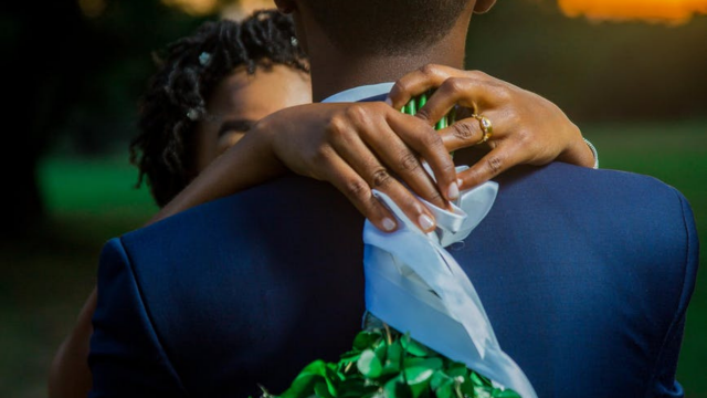 jblack bride draping her hands around the groom's neck with a bouquet